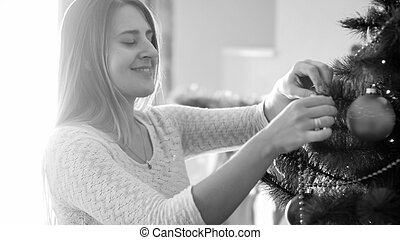 Black and white portrait of smiling young woman adorning Christmas tree