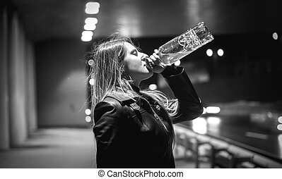 black and white portrait of woman drinking whiskey at night on street