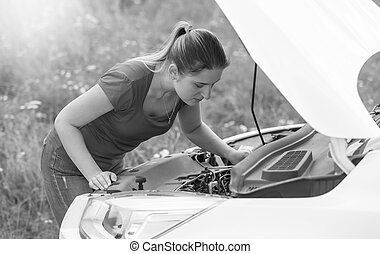 Black and white portrait of woman looking on the motor of broken car in field