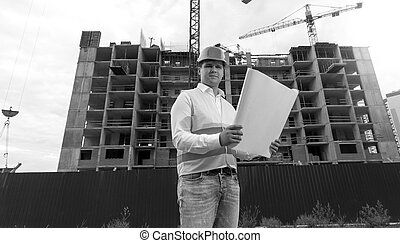 Black and white portrait of young engineer in hardhat with blueprints on building site
