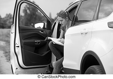 Black and white portrait of young woman got lost on the countryside road looking for correct route in map