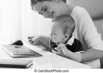Black and white portrait of young woman taking care of baby at office
