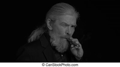 Black and white portrait Stylish business elderly man smokes a cigar in dark business clothes in a semi-lit room on a black background. Prores 422.
