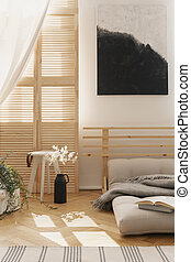 Black and white poster above grey bed in bright bedroom interior with stool next to flowers. Real photo