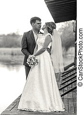Black and white shot of bride and groom posing on pier at river