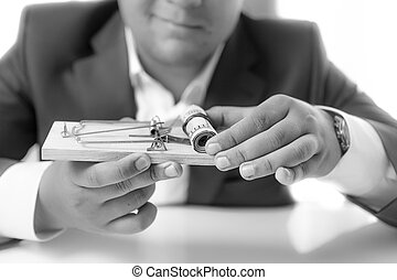 Black and white shot of businessman holding mousetrap with money
