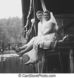 Black and white shot of newlyweds sitting on pier and...
