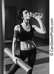 woman with yoga mat drinking water