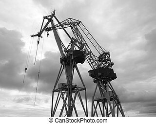 black and white silhouettes of cranes in the shipyard.