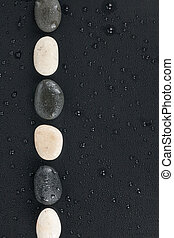 Black and white stones lie on a wet black background