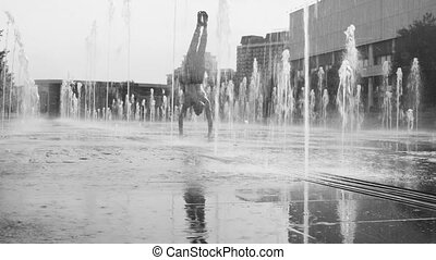 Strong man performing handstand in the fountain - Black and...