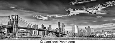 Black and white view of airplane over New York City. Tourism concept