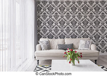 Comfortable sofa by the black and white wall with ornaments