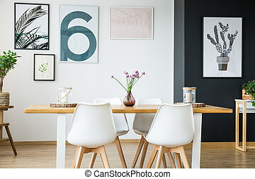 Black and white wall with posters in spacious dining room