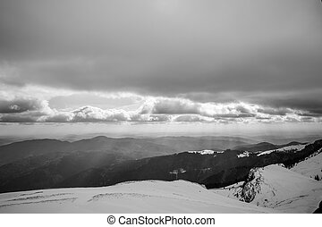 Black and white winter landscape over Carpathian Mountains. Panorama of snow mountain range landscape with light coming from sky over Carpathian Mountains.