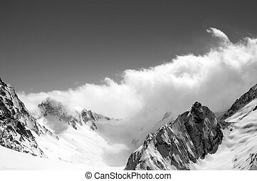 Black and white winter snowy mountains in cloud
