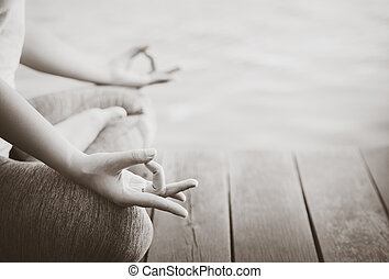 Black and white woman yoga finger acting on hands with nature surrounding. Concept of healthy lifestyle and relaxation.