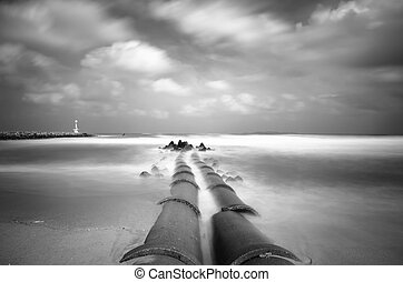 black and white,image of concrete drain pipeline at coastline. soft white wave hitting the beach due to long exposure. lighthouse and break water structure.soft and dramatic white clouds with blue sky