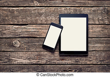 Black Apple devices - Iphone 6 plus and Ipad Air on old wood...