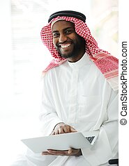 Black Arabic man working on laptop