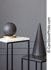 Black, art deco sculptures on metal stands against gray wall with molding in an elegant, modern gallery. Real photo