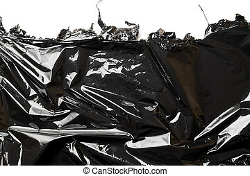Black background. Black shiny film bag pattern isolated on white with copy space. Wrap transparent dark cellophane texture. Creative crumpled background.