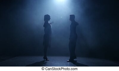 Black background. Dance element from the rumba, silhouette couple ballroom