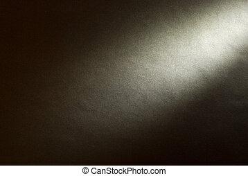 Black background illuminated from the right corner spotlight