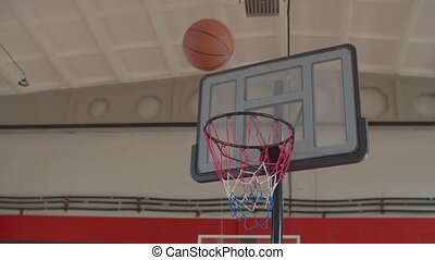 Athletic african american basketball player in uniform driving to the hoop, cathing pass in the air from teammate and performing alley oop dunk during basketball game on indoor court.