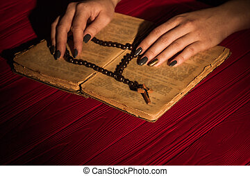 Black bead rosary on the old opened holy bible book.