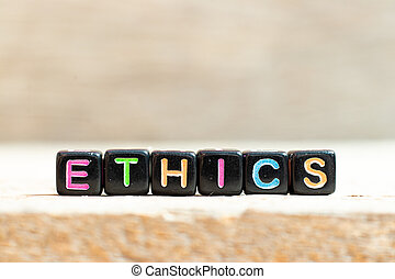 Black bead with color letter in word ethics on wood background