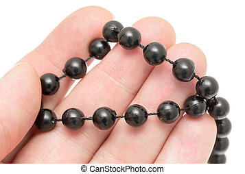 Black beads in hand on a white background