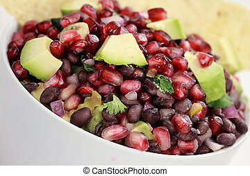 A healthy relish or salsa with pomegranate, avocado, red onions, black beans and cilantro served with corn chips.