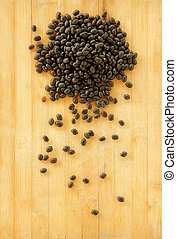 black beans are on wooden background.