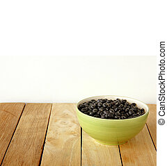 black beens are on wooden background.