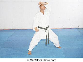 Black belt karate man in defending position