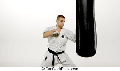 Black belt karate man practicing on the sandbag on white background. Slow motion.