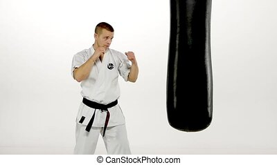 Black belt karate man practicing on the sandbag on white background. Slow motion