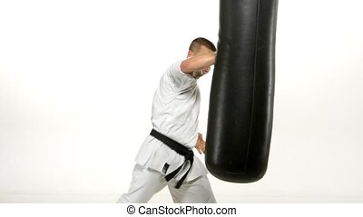 Black belt karate man practicing on the sandbag on white background