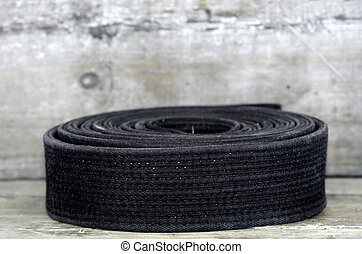 black belt - a black belt on wooden background