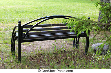 Black bench in the park on a summer day