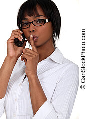 black bespectacled woman on the phone with finger before her mouth
