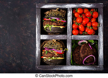 Black big sandwich - black hamburger with juicy beef burger, cheese, tomato, and red onion in box on black background. Flat lay. Top view