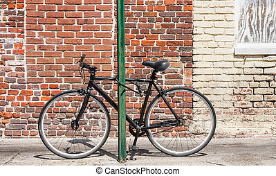 Black Bike Chained to Green Post