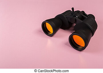 binoculars with orange lens on pink background