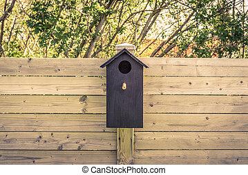 Black bird house on a fence
