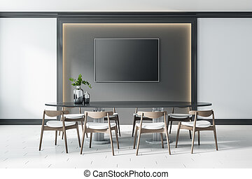 Black blank screen in the center of dark wall panel with lights around and big table with modern wooden chairs on ceramic floor tiles. Mock up