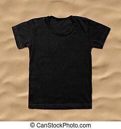 Black blank t-shirt on sand background