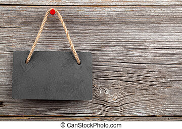 Black board of slate on old rustic wooden background.