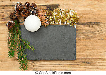 black board with Christmas decoration on brown wooden background
